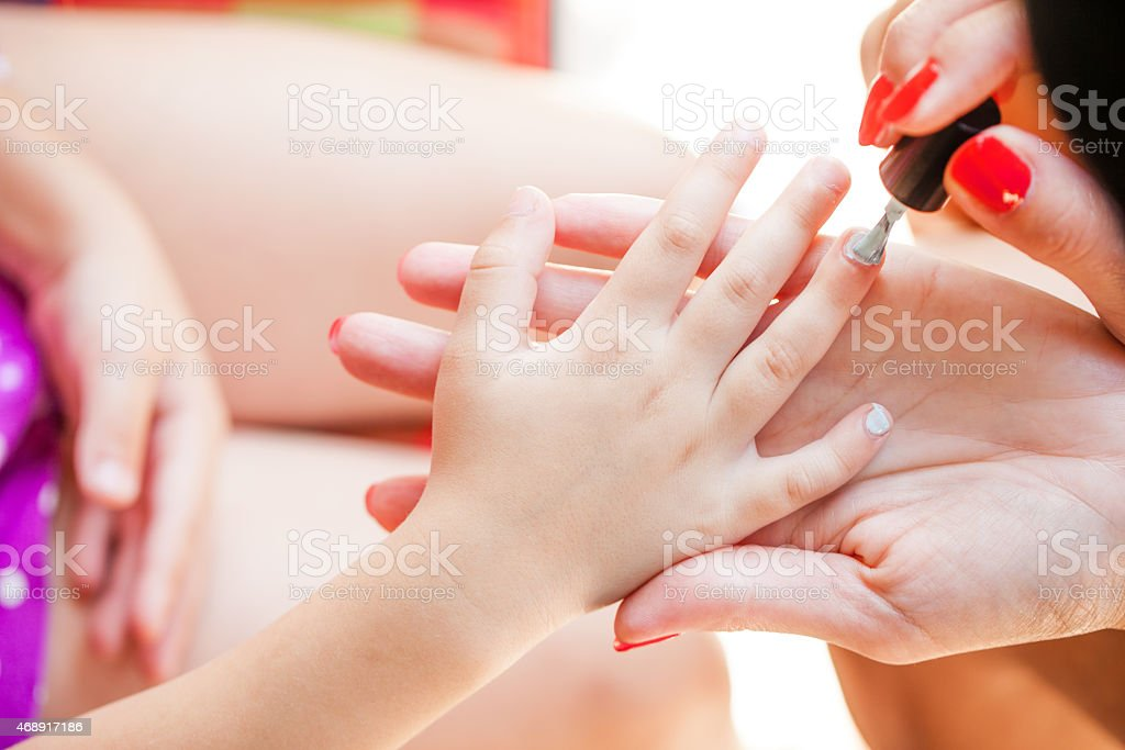 Mother applying nail polish to her daughter stock photo