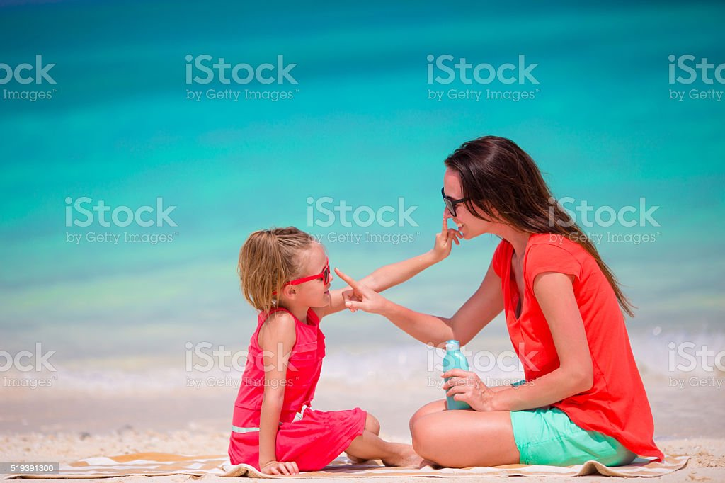 Mother applying sun protection cream to daughter at tropical beach stock photo