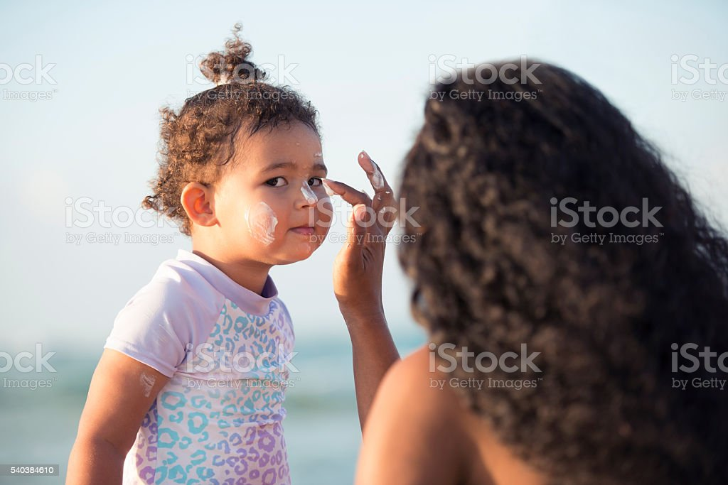 Mother applying sun protection on her baby girl's face. stock photo