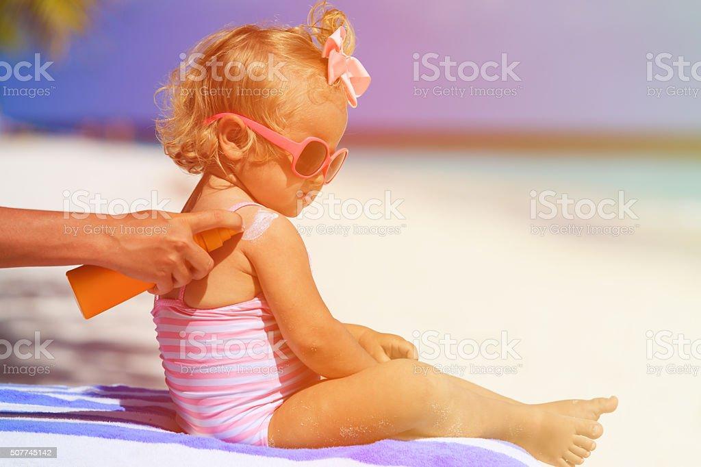 mother applying sunblock cream on daughter shoulder stock photo