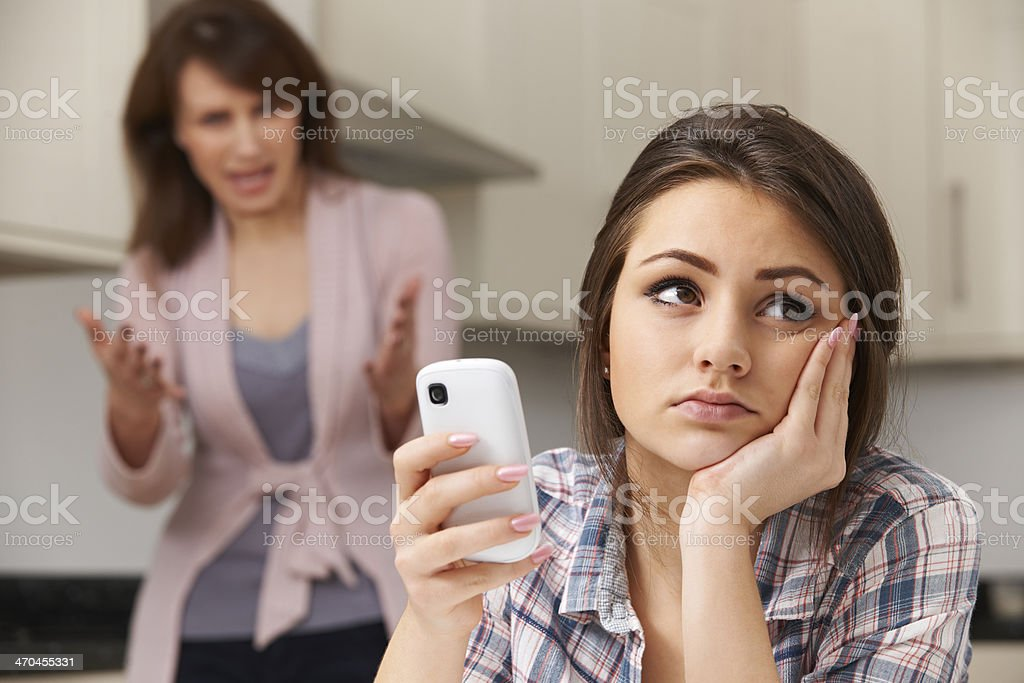 Mother Arguing With Daughter Over Use Of Mobile Phone stock photo