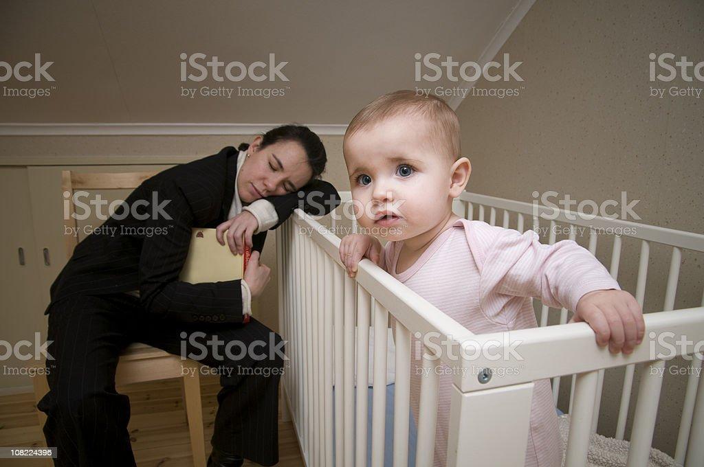 Mother Asleep on Crib with Baby Awake and Watching stock photo