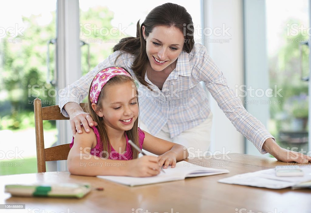 Mother assisting girl (8-9) with school homework royalty-free stock photo