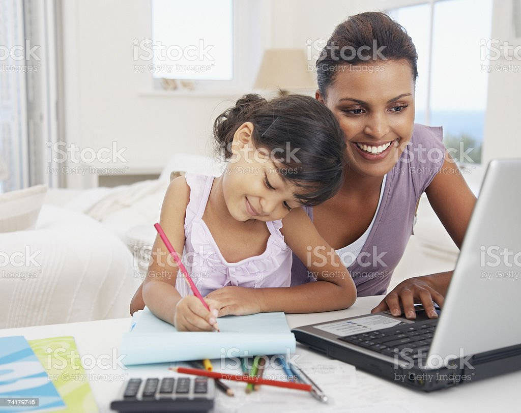 Mother at laptop with daughter drawing royalty-free stock photo