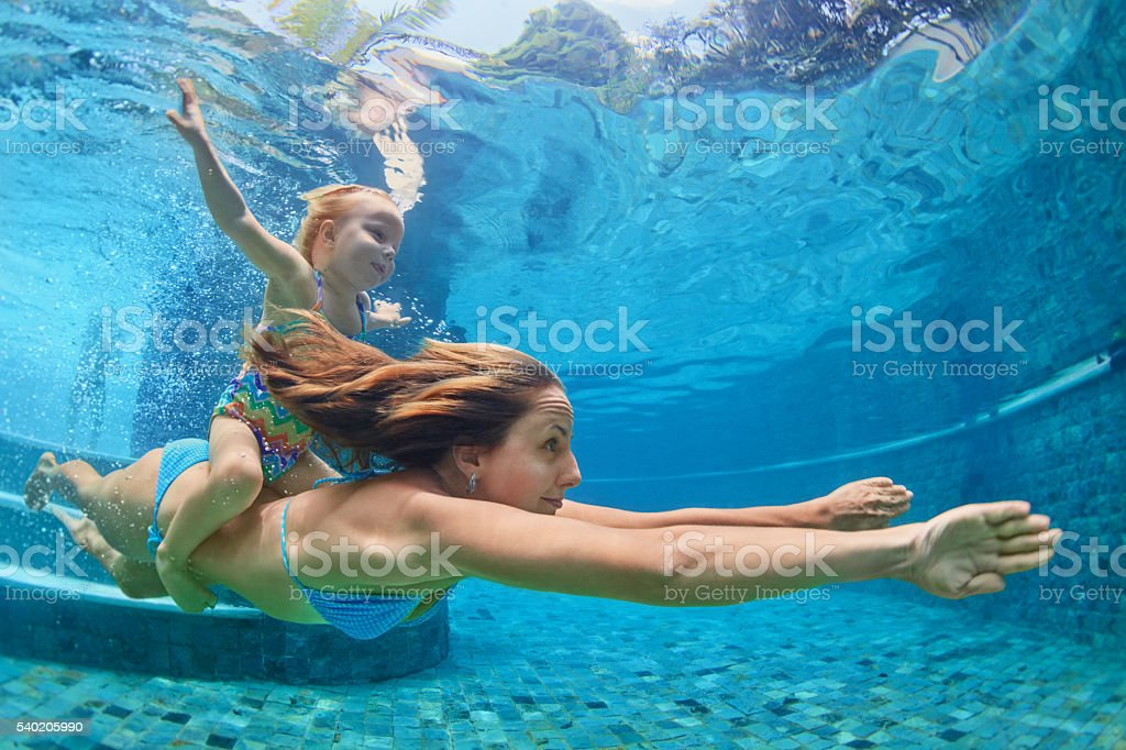 Mother, baby girl swim and dive underwater in pool stock photo