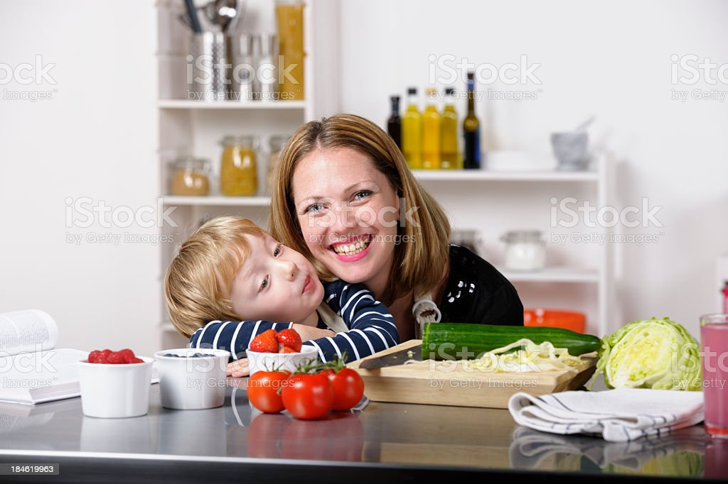 Mother Balancing Childcare And Meal Preparation royalty-free stock photo