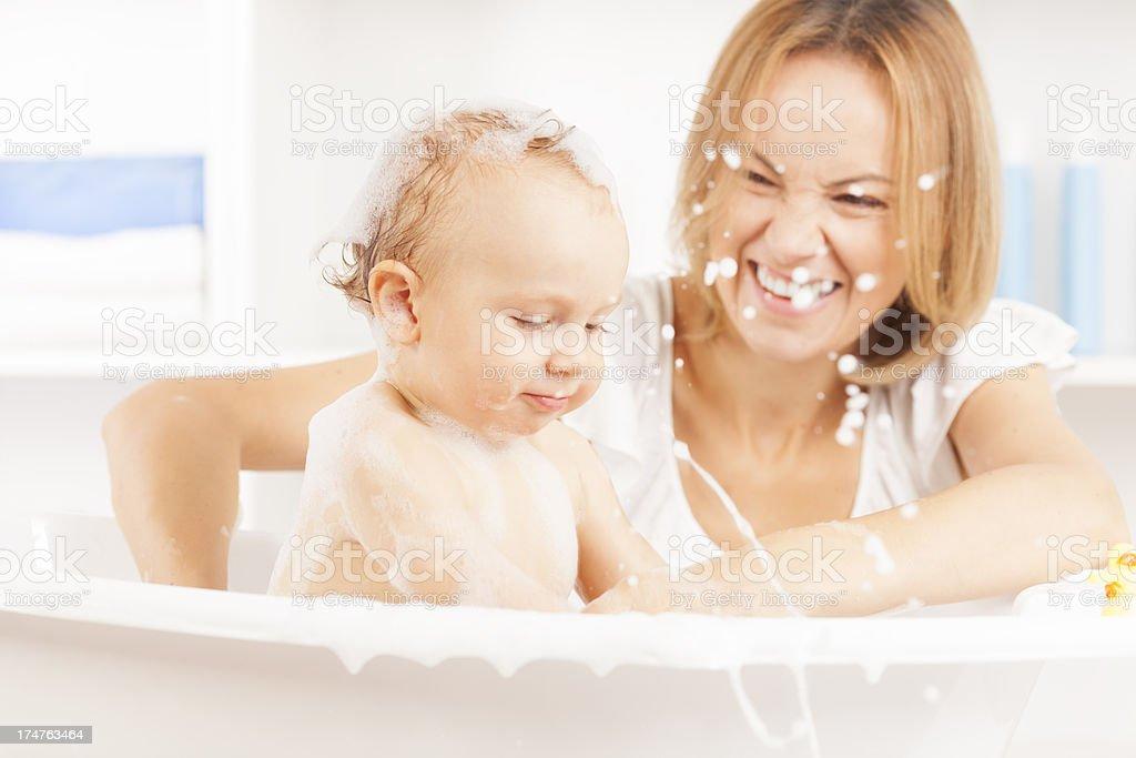 Mother bathing her baby boy stock photo