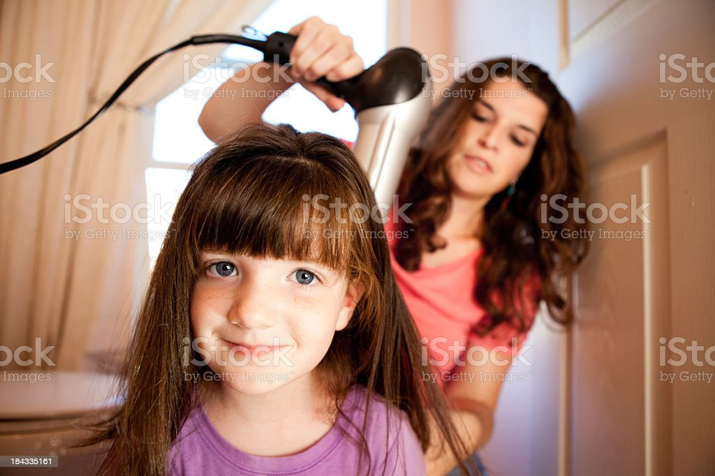 Mother Blow Drying Daughter's Hair in Bathroom at Home royalty-free stock photo