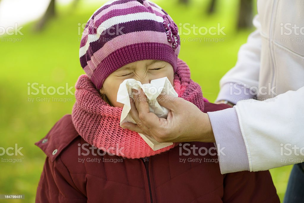 Mother blowing nose of her daughter stock photo