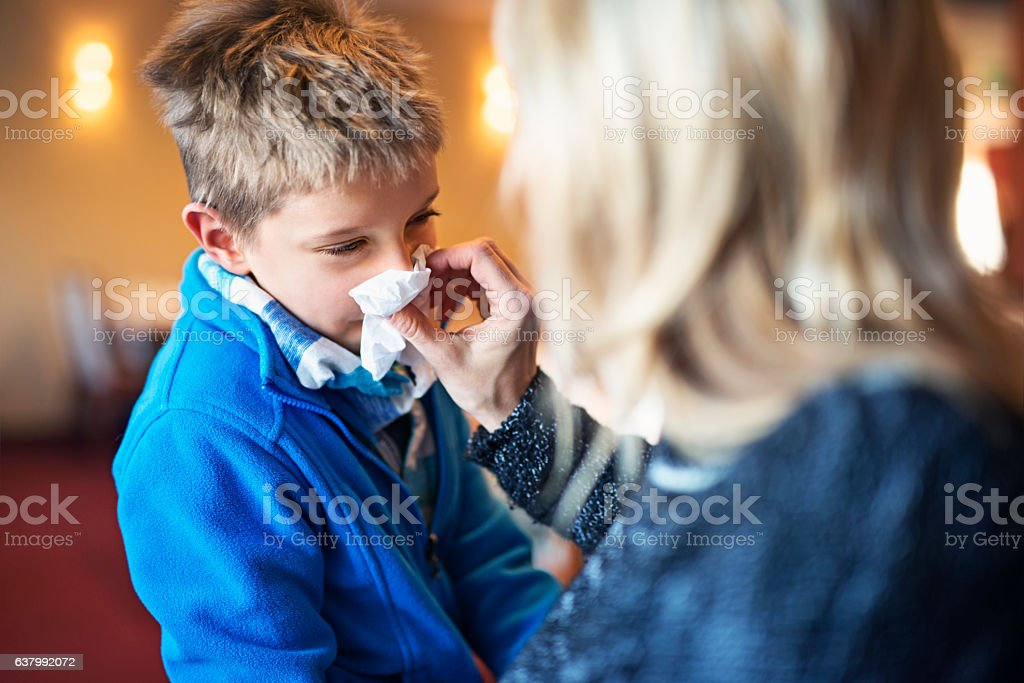 Mother blowing nose of her sick son stock photo