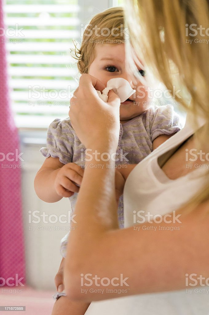 Mother blowing the nose of her baby girl. stock photo