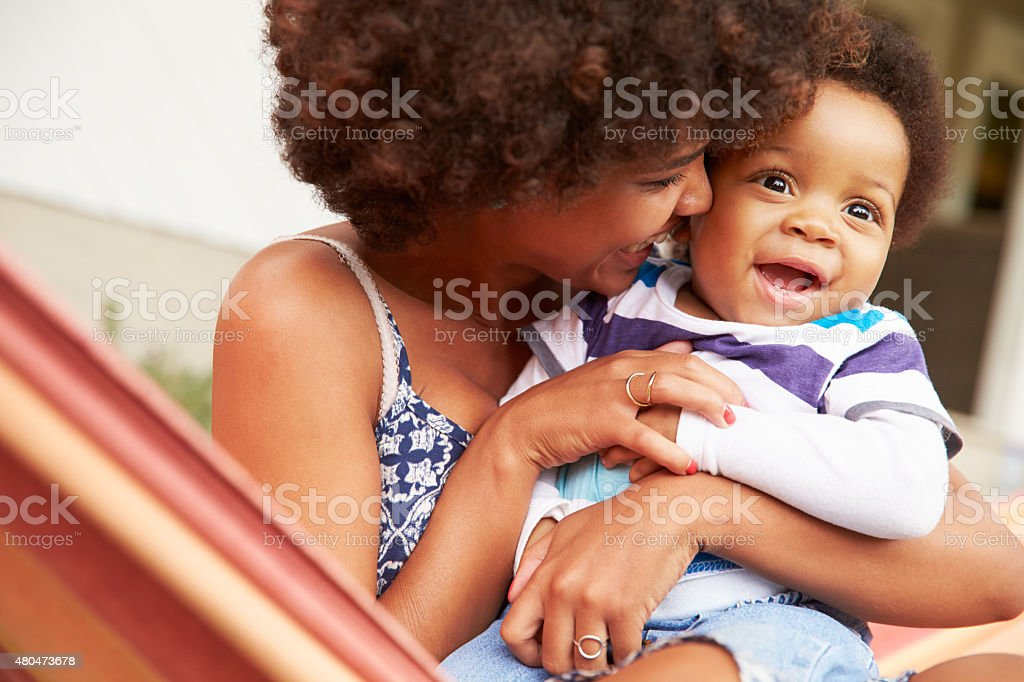 Mother bonding with young son sitting in a hammock stock photo