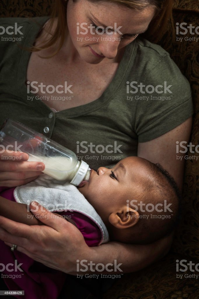 mother bottle feeding multi-ethnic adopted baby daughter royalty-free stock photo