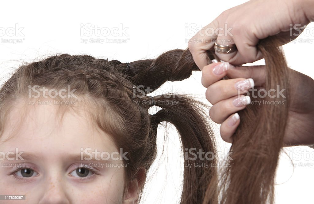 mother braiding one's hair for daughter stock photo