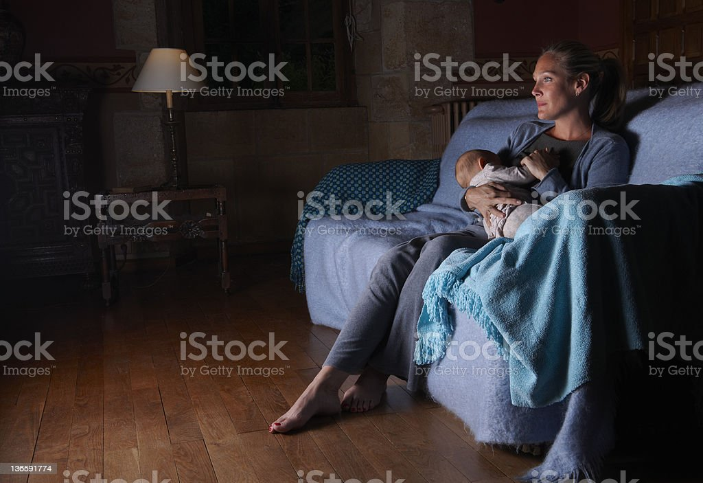 Mother breastfeeding with television stock photo
