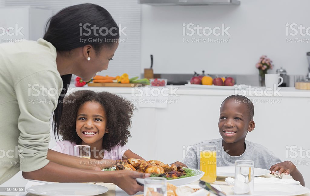 Mother bringing fried chicken to children at the dinner table stock photo