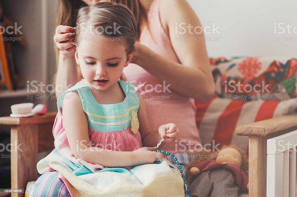 mother brushing toddler daughter hair at home stock photo