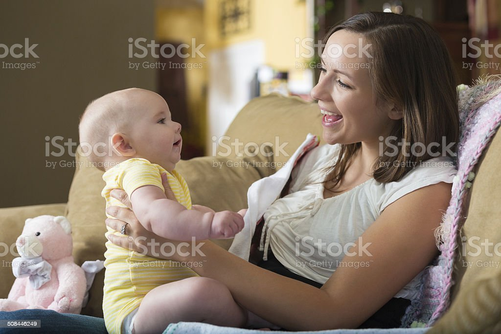 Mother burping baby after breastfeeding, while sitting on sofa stock photo