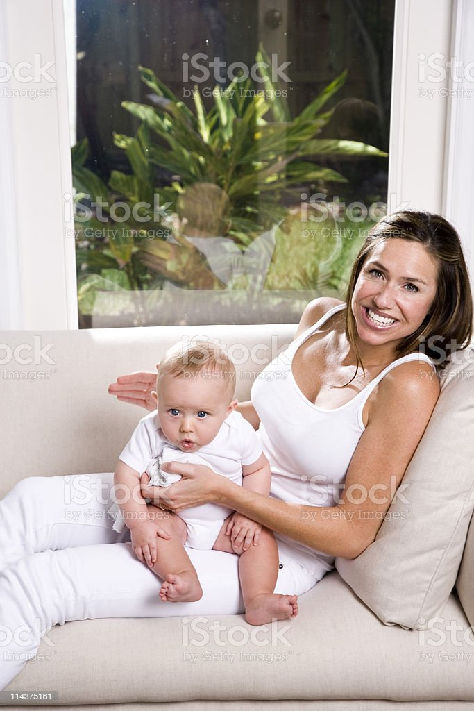 Mother burping six month old baby after a meal stock photo