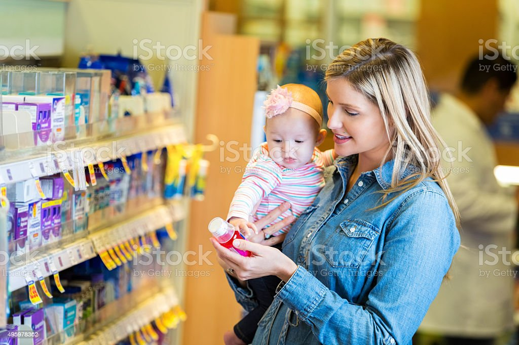 Mother buying cold medicine for baby daughter in pharmacy stock photo