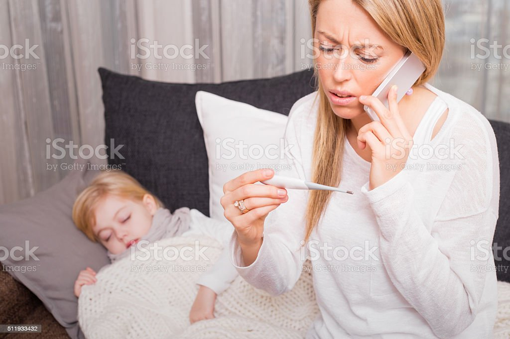 Mother calling doctor and looking at thermometer stock photo