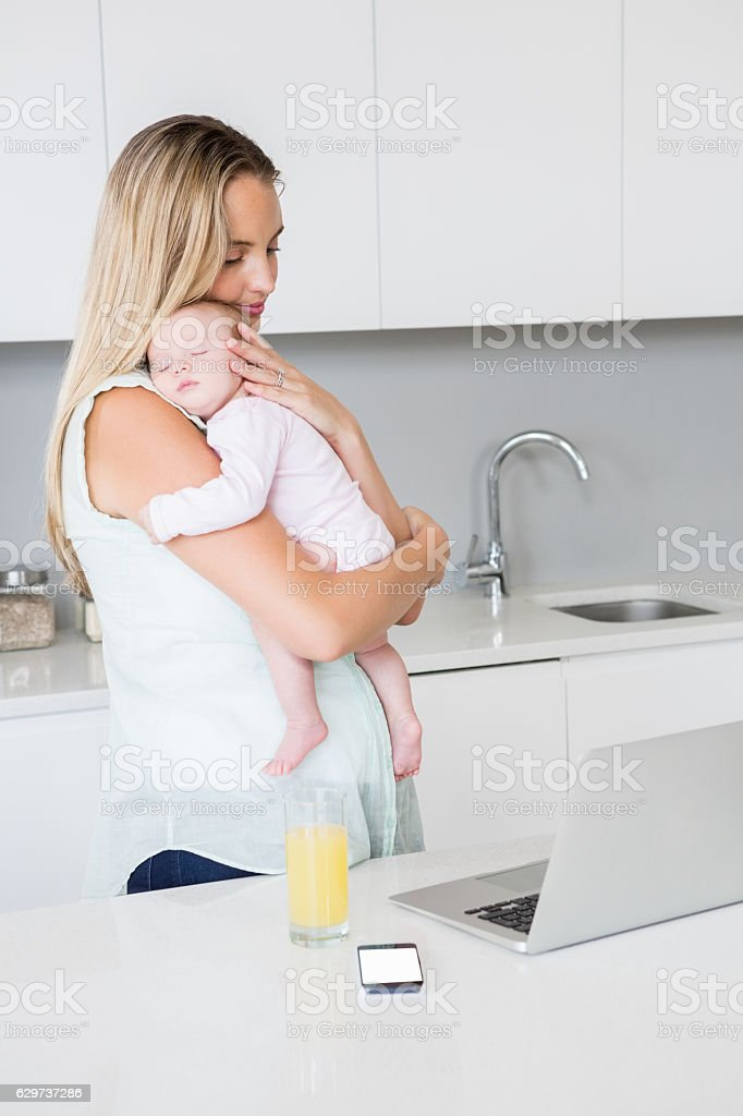 Mother carrying her baby in kitchen stock photo