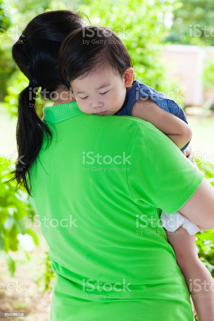 Mother carrying her daughter in home backyard stock photo