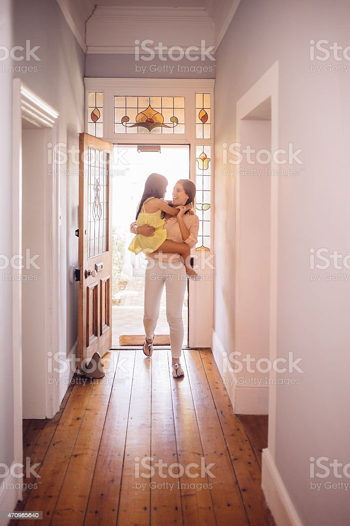 Mother carrying her daughter into the hall of their home stock photo