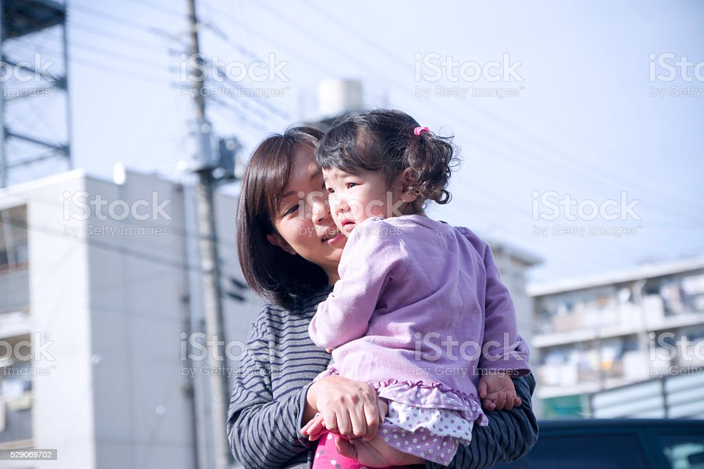 Mother carrying her little daughter stock photo