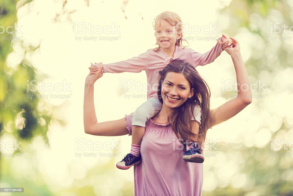 Mother carrying her little girl on shoulders. stock photo