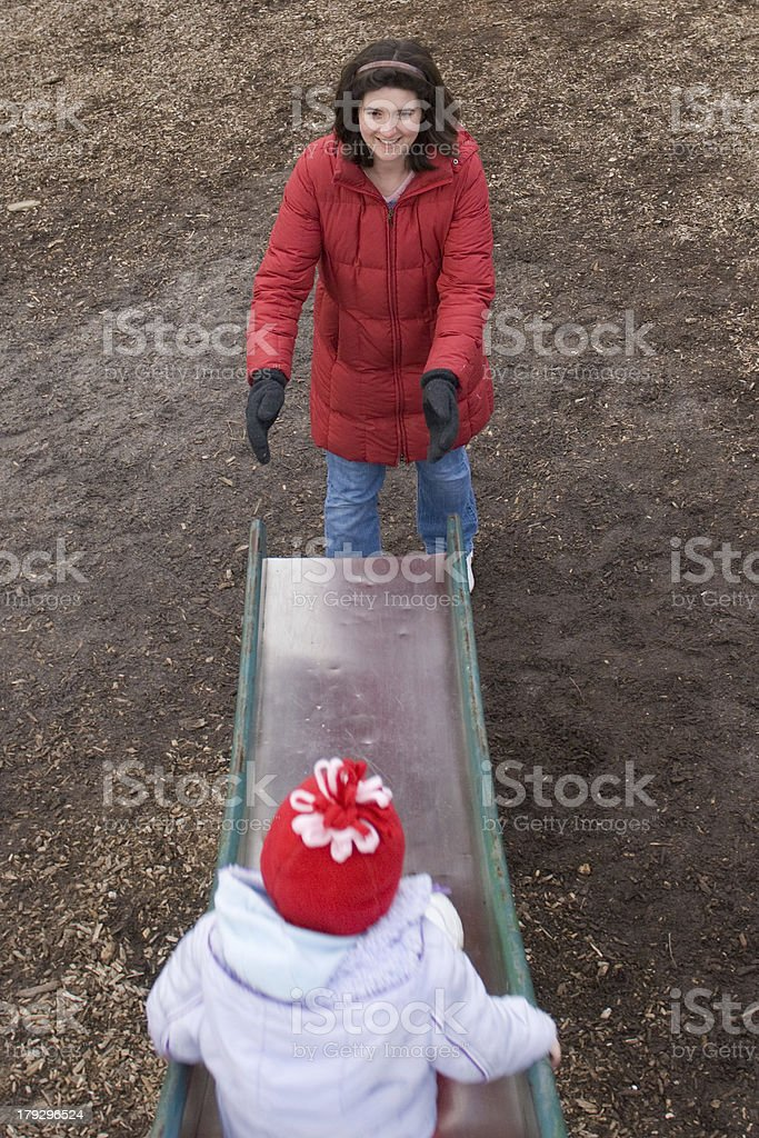 Mother catching toddler on slide stock photo