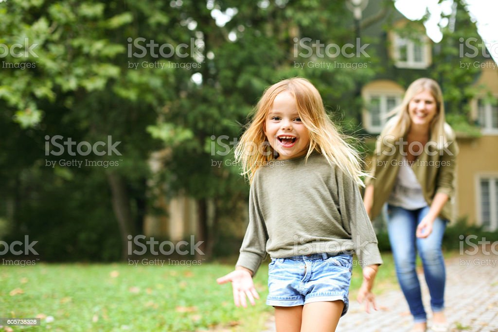Mother chasing girl outdoor. stock photo