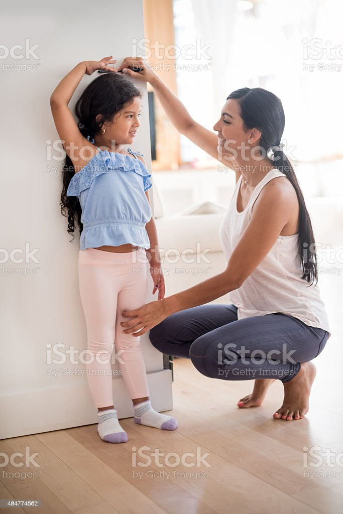 Mother checking daughters height stock photo
