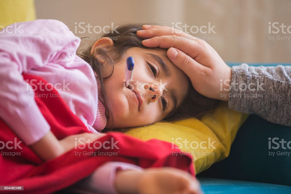 Mother checking on sick daughter laying in bed stock photo
