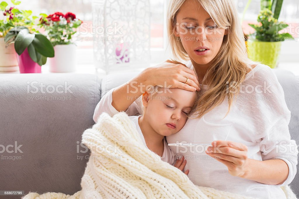 Mother checking temperature of her sick child stock photo