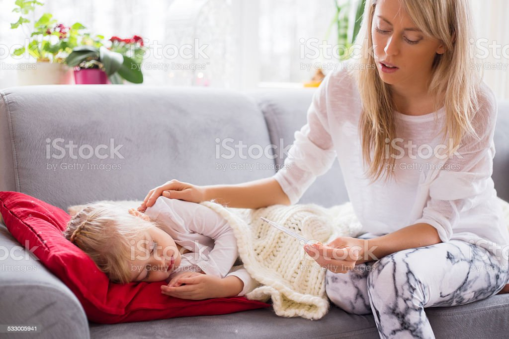 Mother checking temperature of her sick little girl stock photo