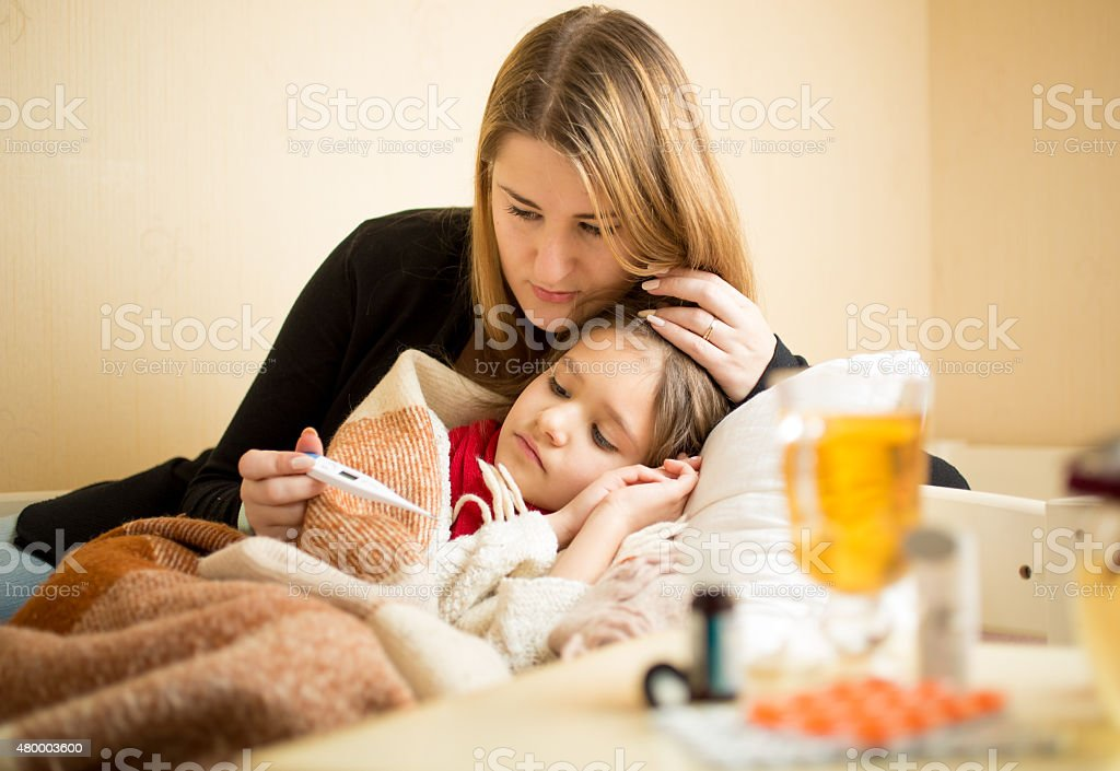 mother checking temperature of sick daughter lying in bed stock photo