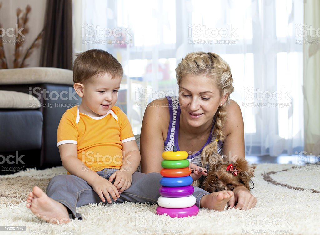 mother, child boy and pet dog playing together indoor royalty-free stock photo