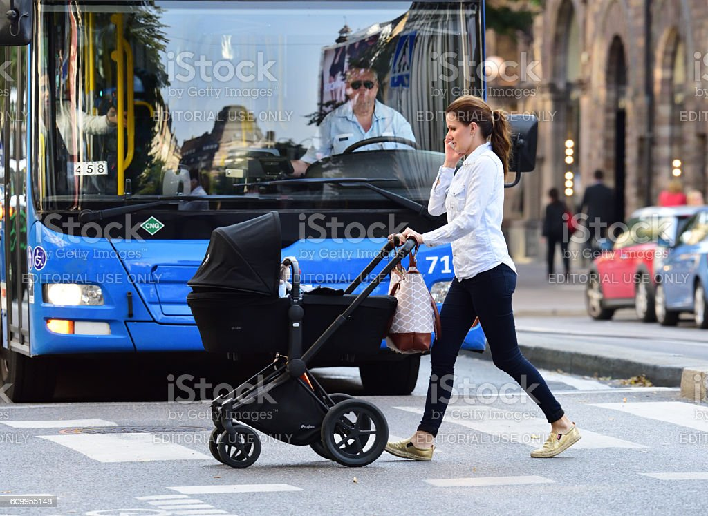 Mother, child in stroller, crossing street, bus and traffic background stock photo