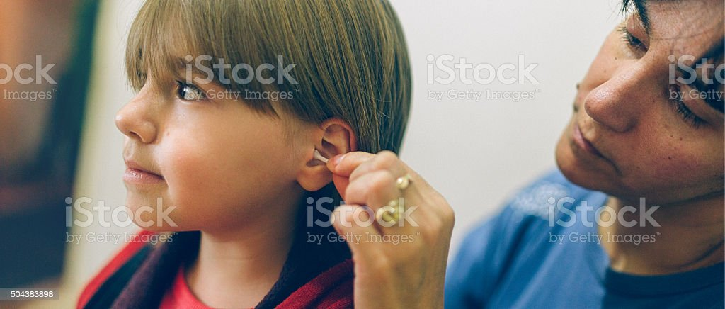 mother cleaning ears her daughter after bathing stock photo