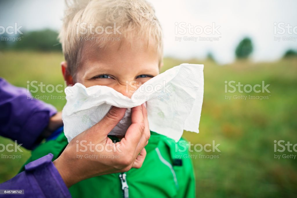 Mother cleaning nose of sick boy stock photo
