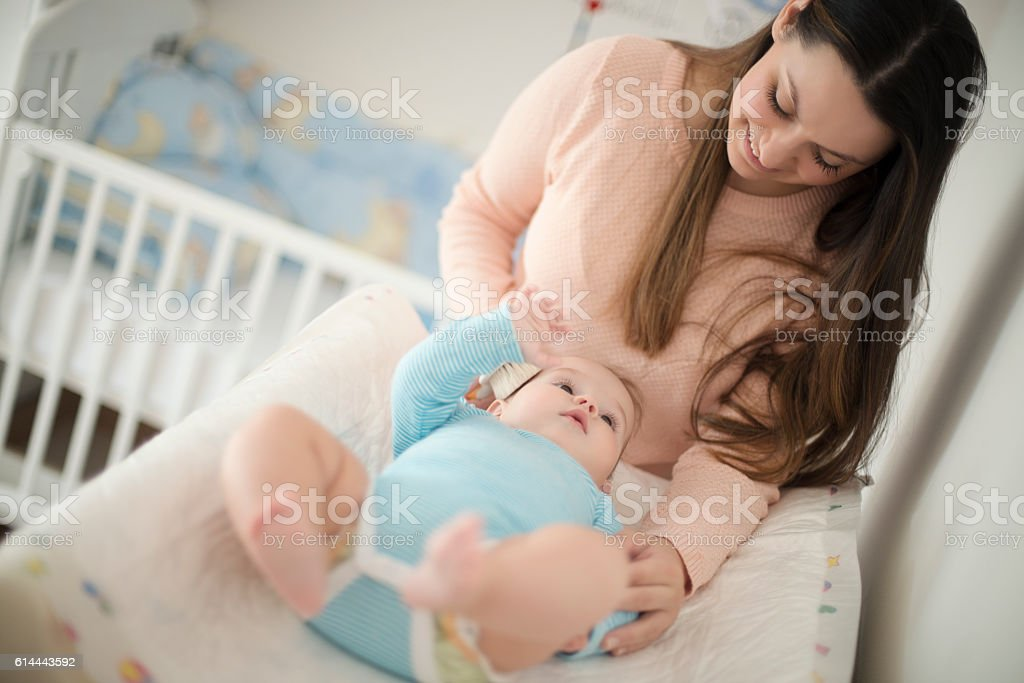Mother combing her baby stock photo