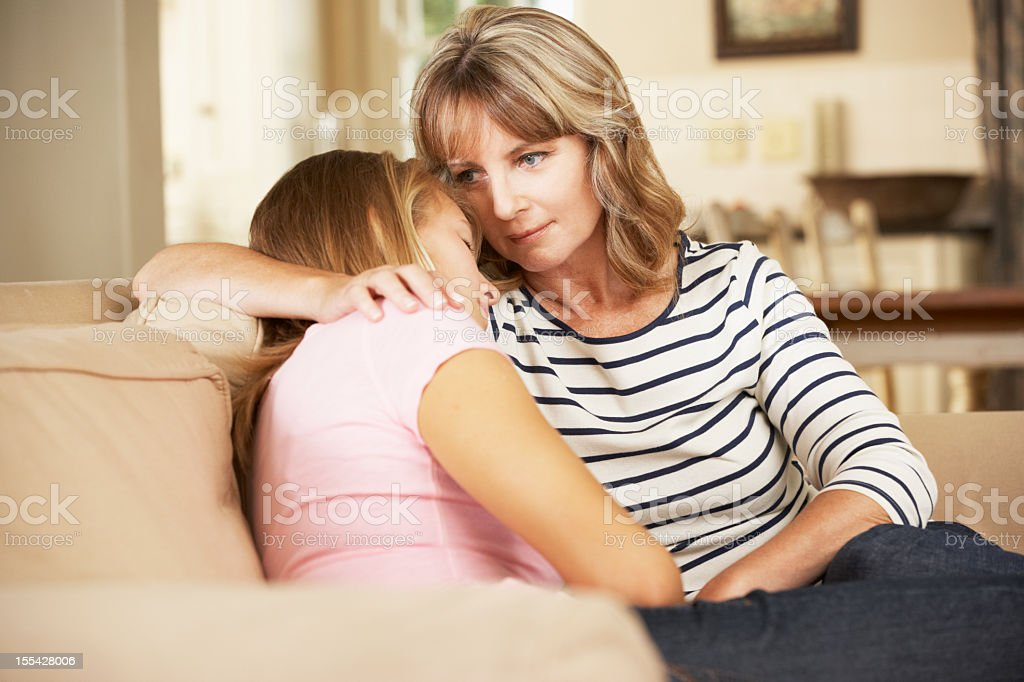 Mother Comforting Teenage Daughter Sitting On Sofa At Home royalty-free stock photo