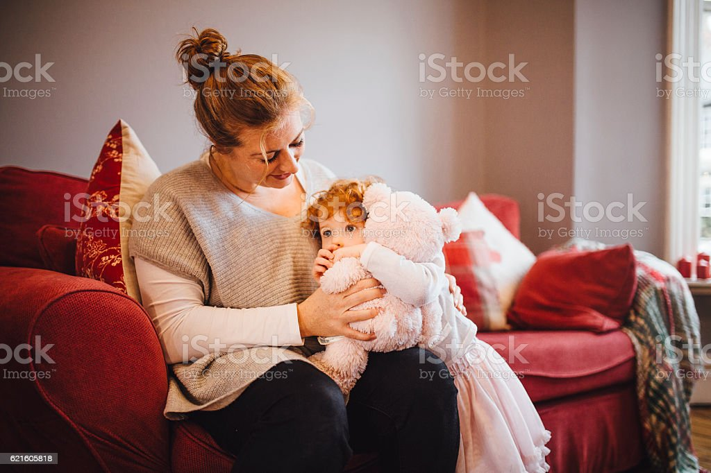 Mother Comforts Daughter on Sofa at Home stock photo