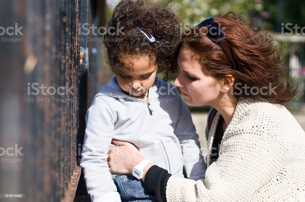 Mother consoling unhappy 4 year old daughter stock photo