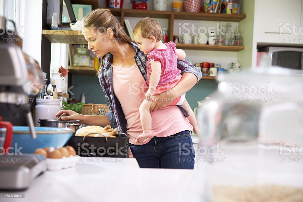 Mother Cooking Meal Whilst Holding Daughter In Kitchen stock photo