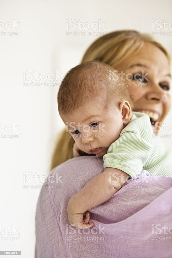 Mother cradling infant on shoulder stock photo