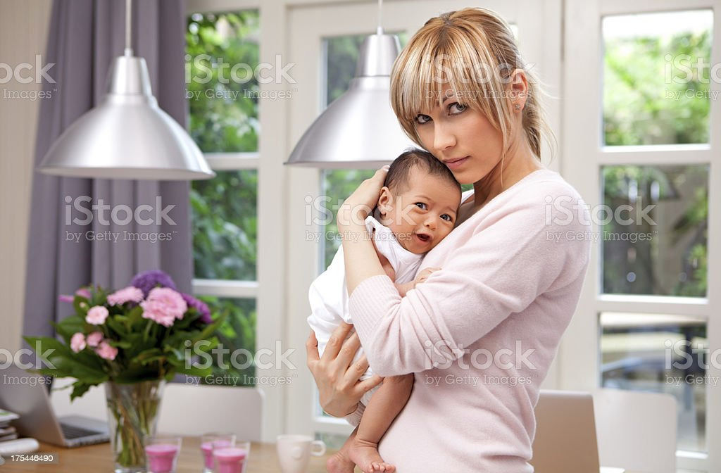 mother cuddling crying baby stock photo