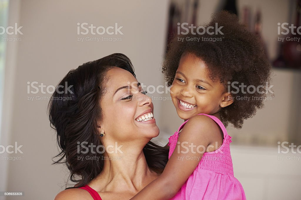 Mother Cuddling Daughter At Home stock photo