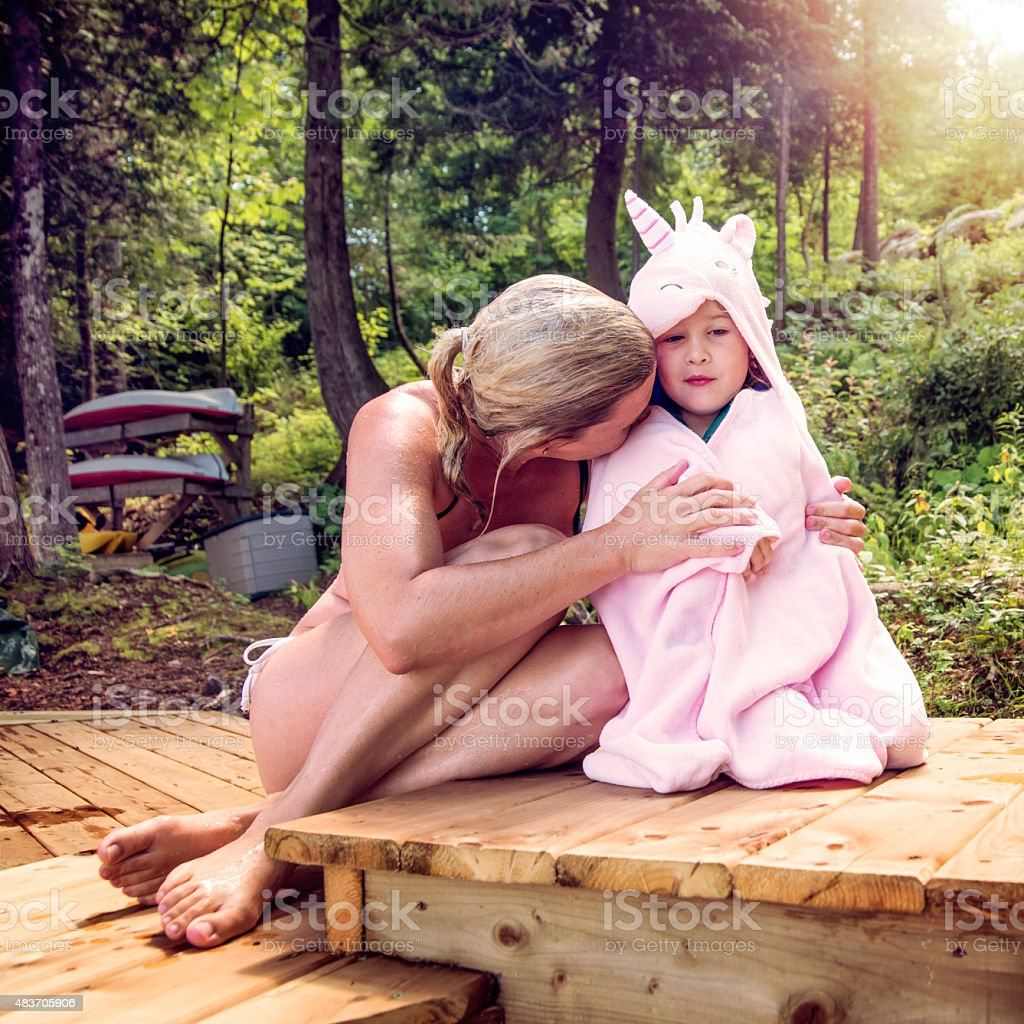 Mother cuddling little daughter after swim in summer nature. stock photo